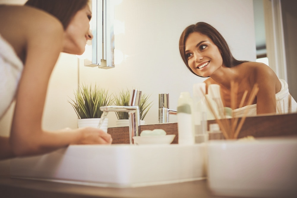 Person with Clear Skin Smiling in Mirror