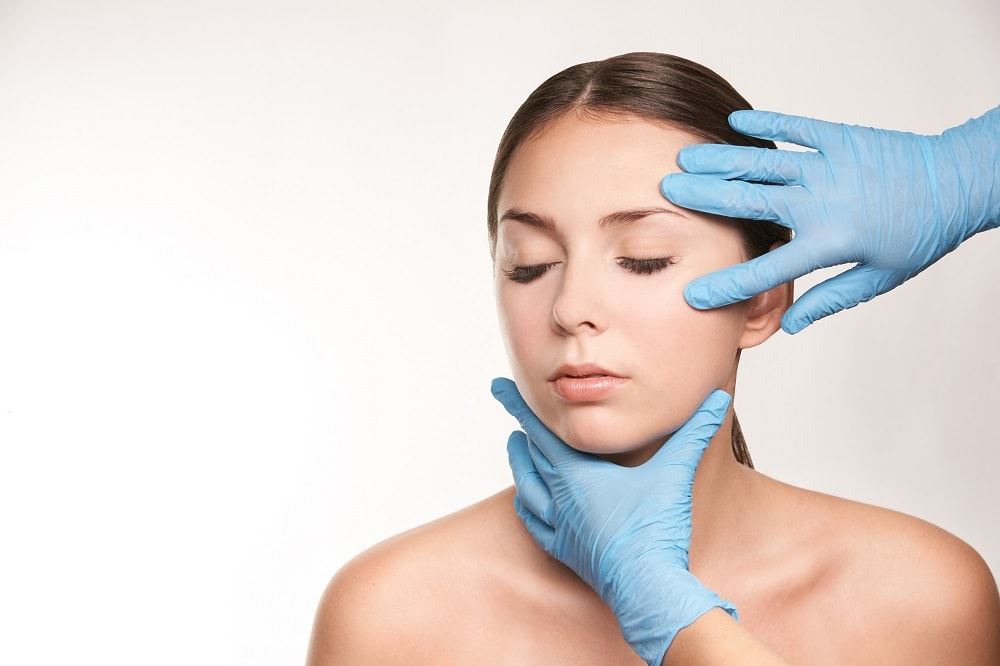 Dermatologist with Blue Rubber Gloves On Checking Woman's Face